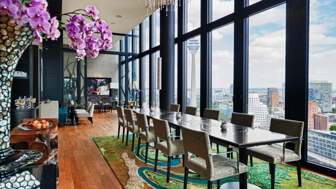 Tables and chairs by windows in hotel lounge