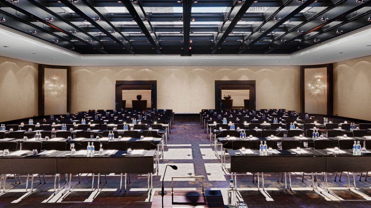 Rows of chairs in large hotel ballroom with glass ceiling