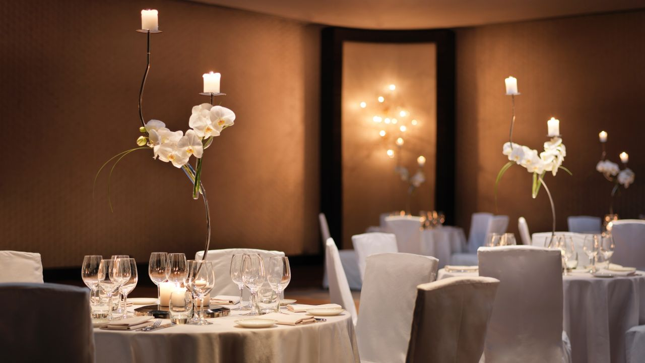 Chairs at linen covered tables with place settings in hotel ballroom