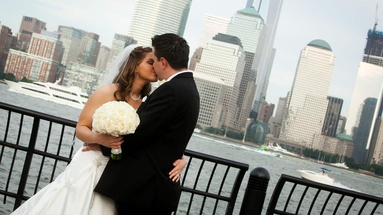 Bride and groom kissing alongside the Hudson River with NYC skyline view