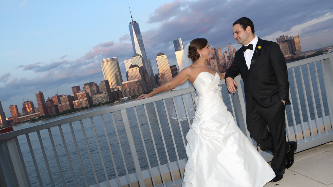Bride and groom posing along the Hudson River with a NYC skyline view