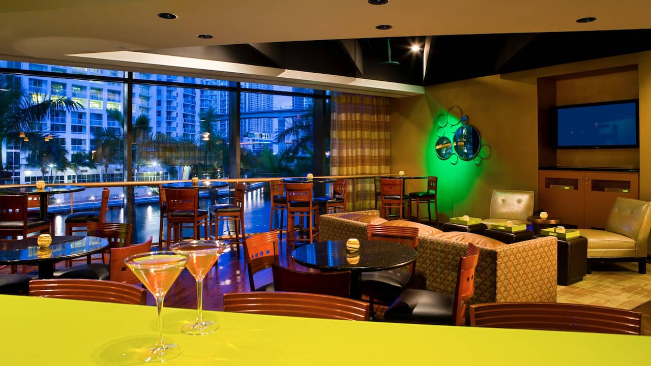 A bar counter at the Riverwalk Bar & Grill with a view of downtown Miami and the riverwalk