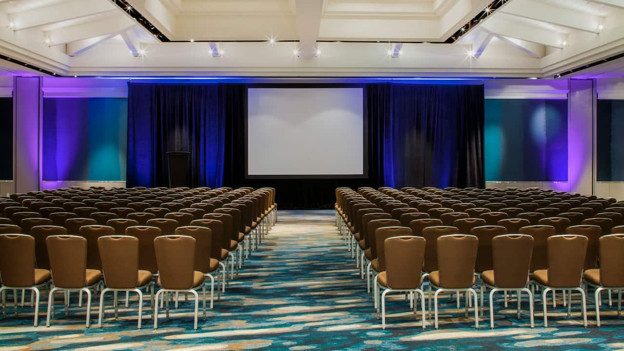 Spacious grand ballroom with beautiful stage lighting and projector