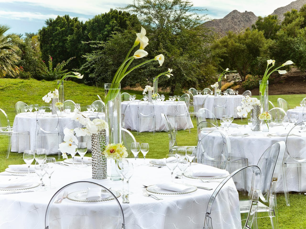 An outdoor wedding reception with white draped tables, flowers, and wine glasses in Palm Springs