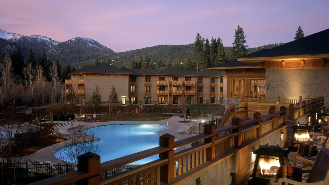 Exterior of the hotel at night with pool and mountain views