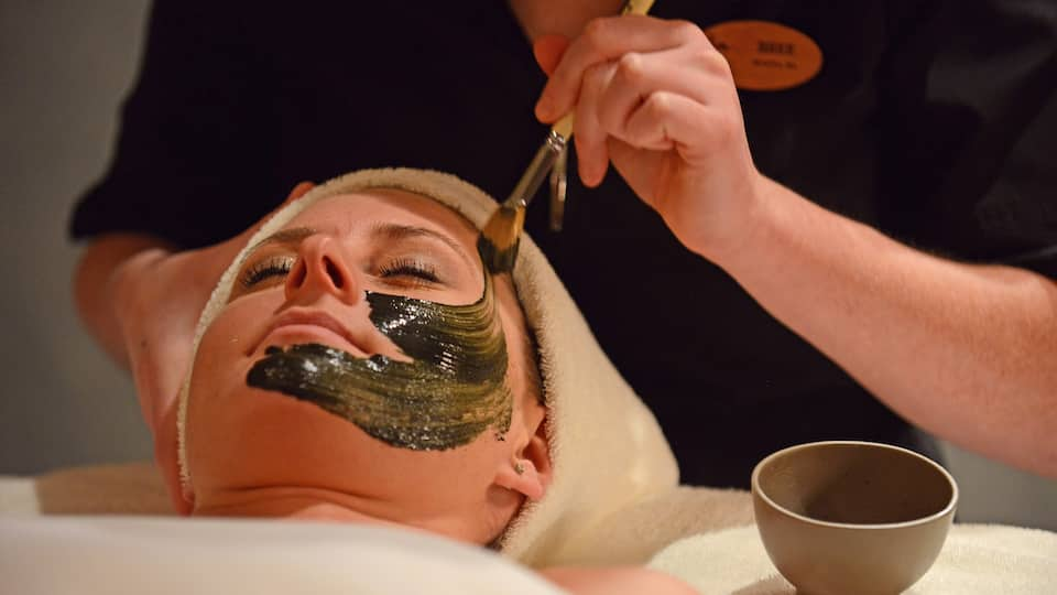 Aesthetician applying a facial mask at Stillwater Spa