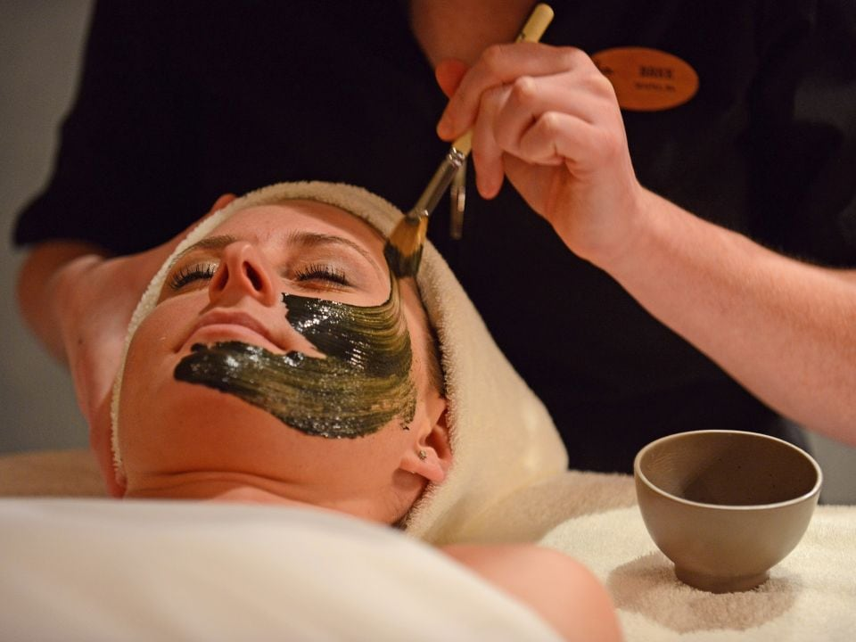 Aesthetician applying a facial mask at Stillwater Spa