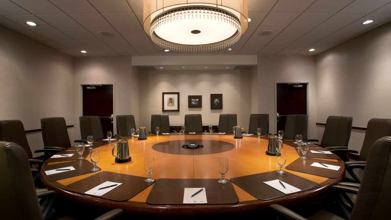 Chairs at large round table in boardroom
