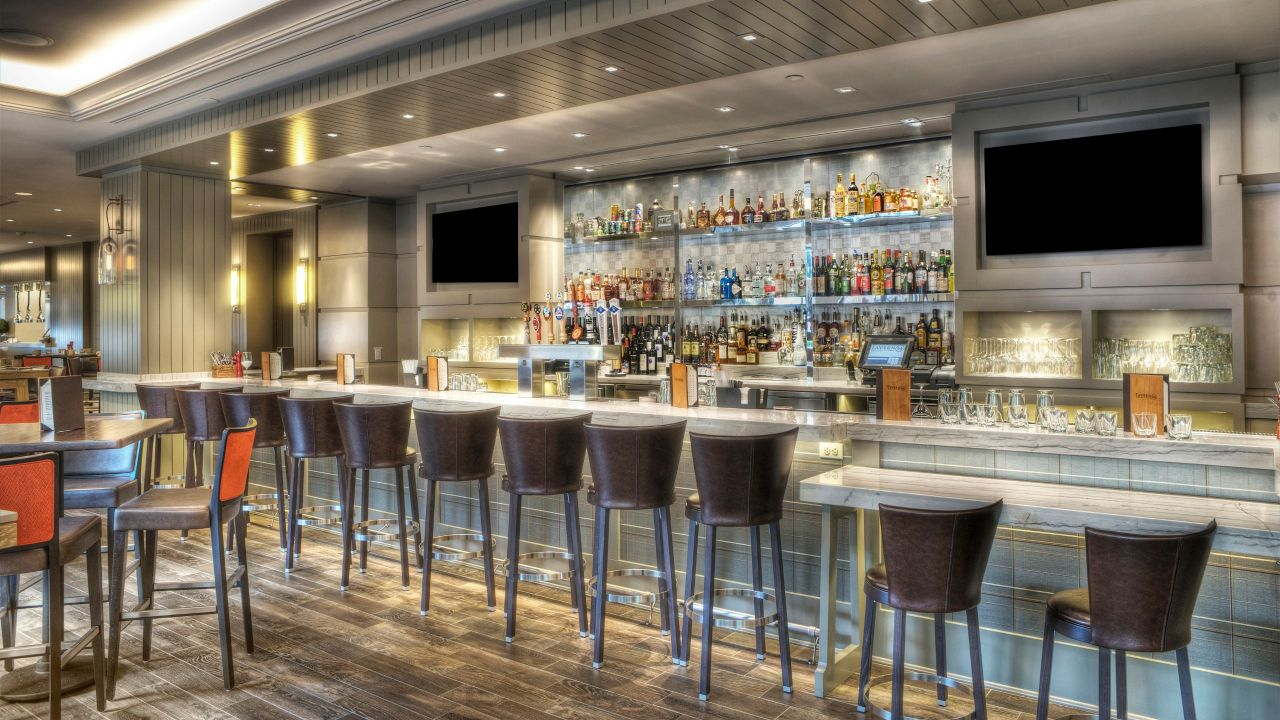 Row of barstools at bar fully stocked with alcohol at Lobby Bar and Lounge at Hyatt Regency Reston