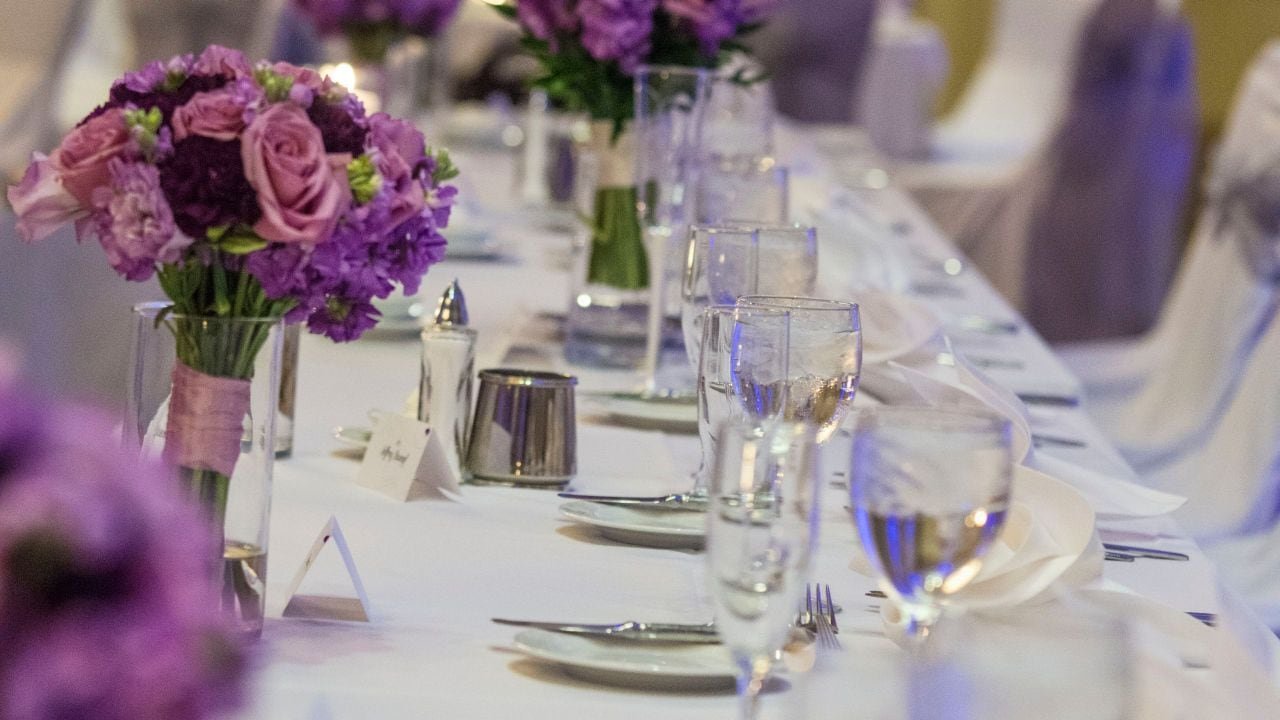 Place settings and purple flower bouquets on table