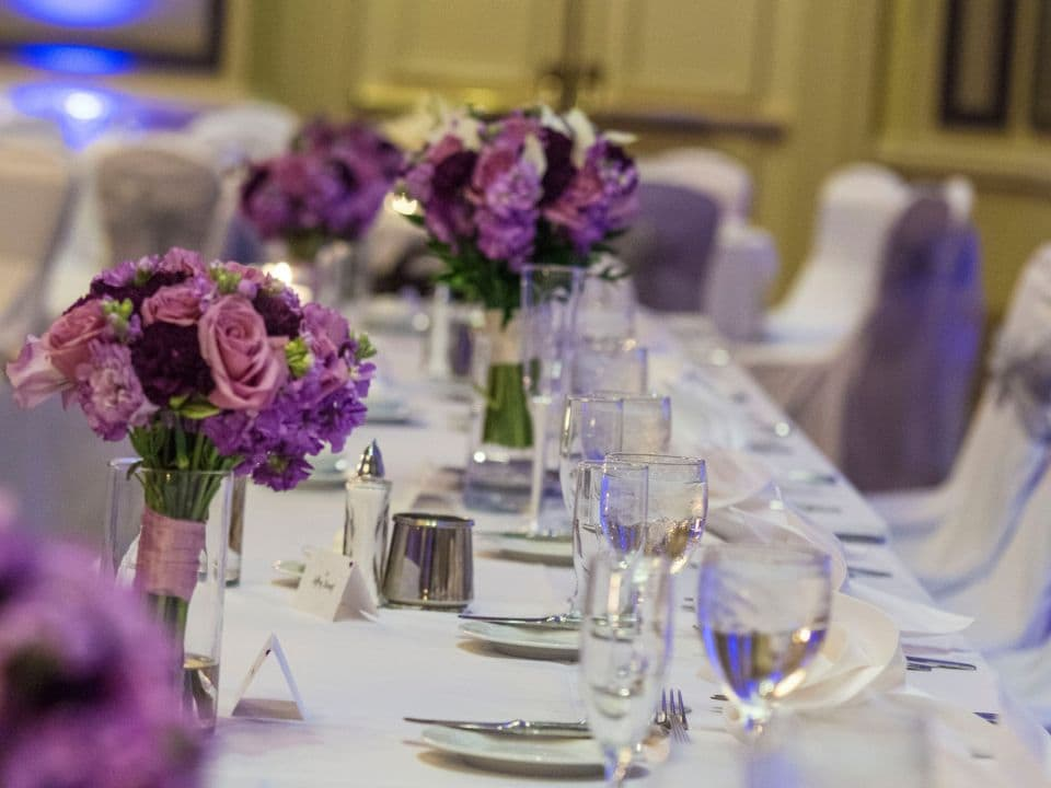 Wedding table set up with place setting and purple flower bouquets