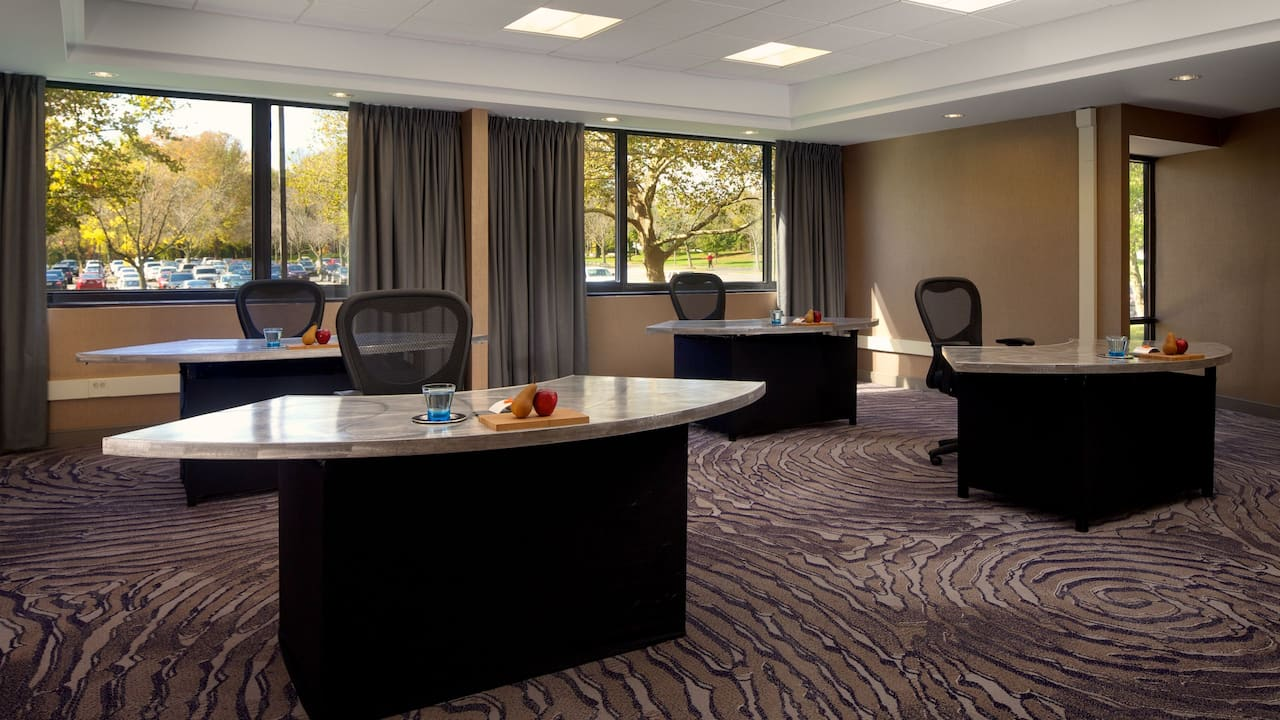 Four tables with office chairs in hotel meeting room