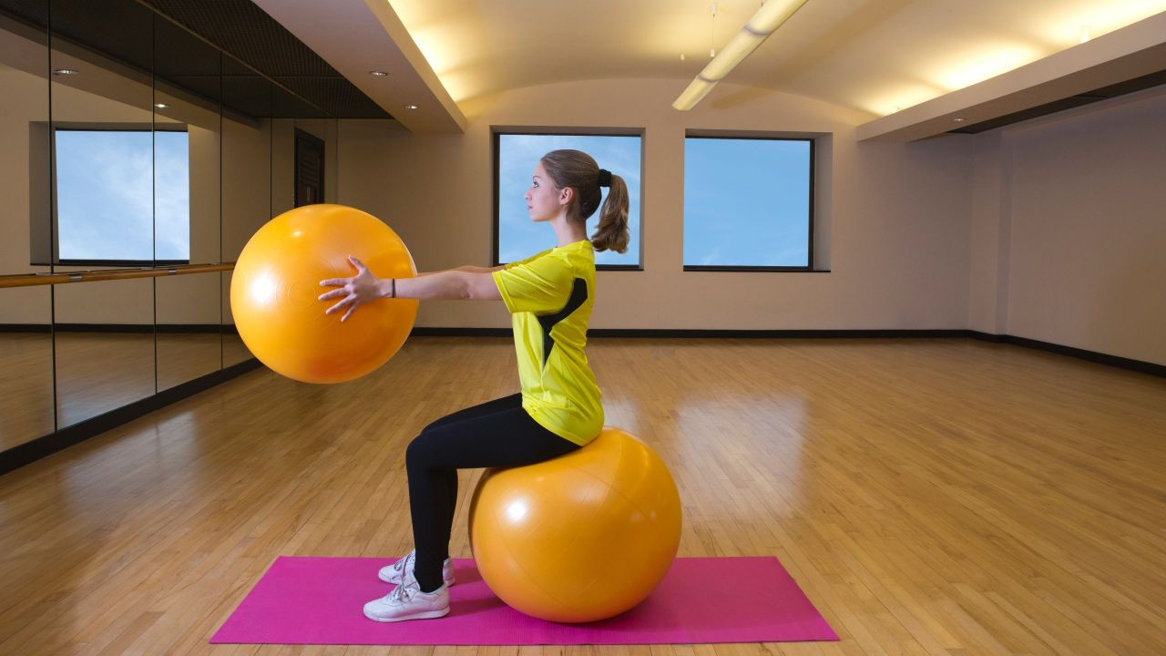 Woman holding and sitting on fitness ball in aerobics studio