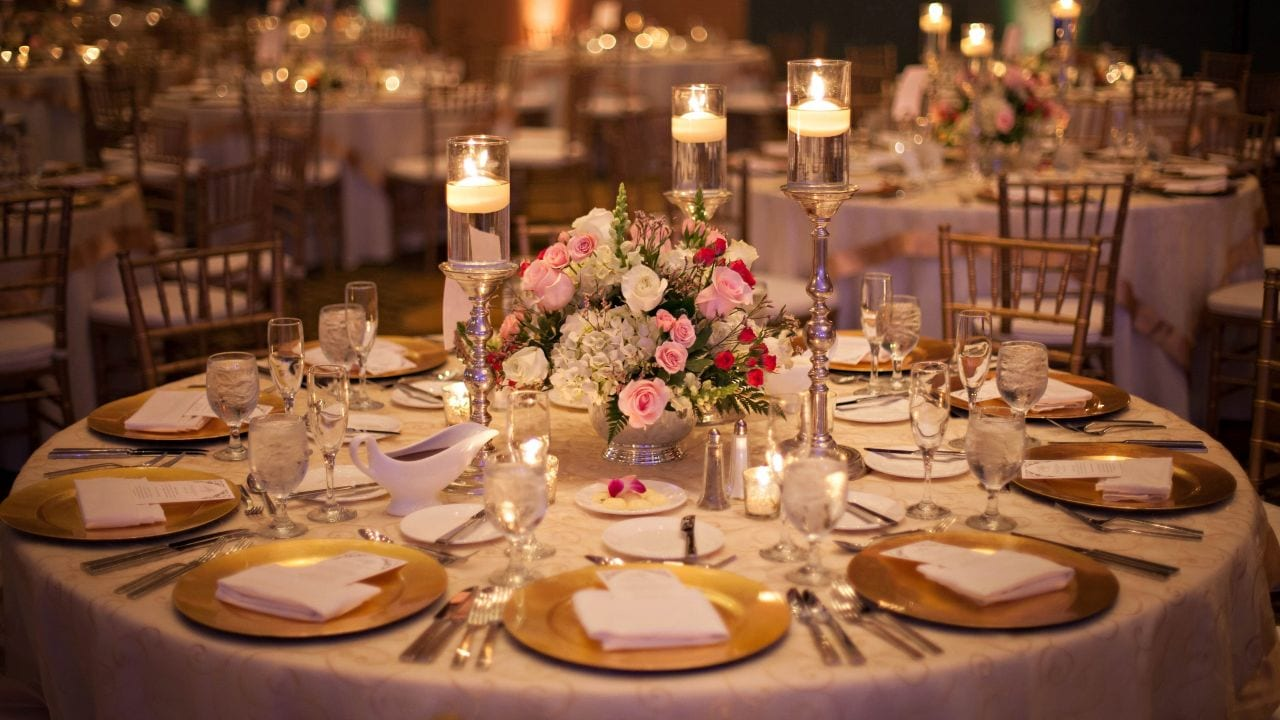 Lazo Wedding table with place settings, pink flowers, and candles