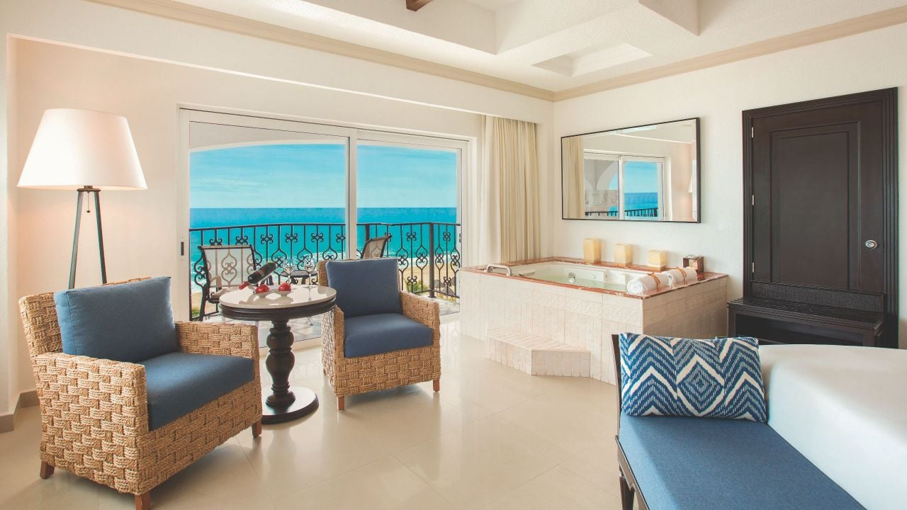 Bed and living area in resort suite with oceanfront view from patio
