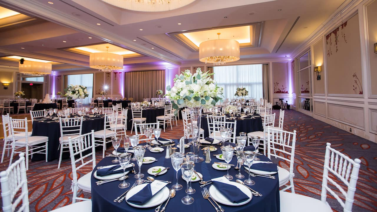 Round table with wedding place setting in hotel ballroom