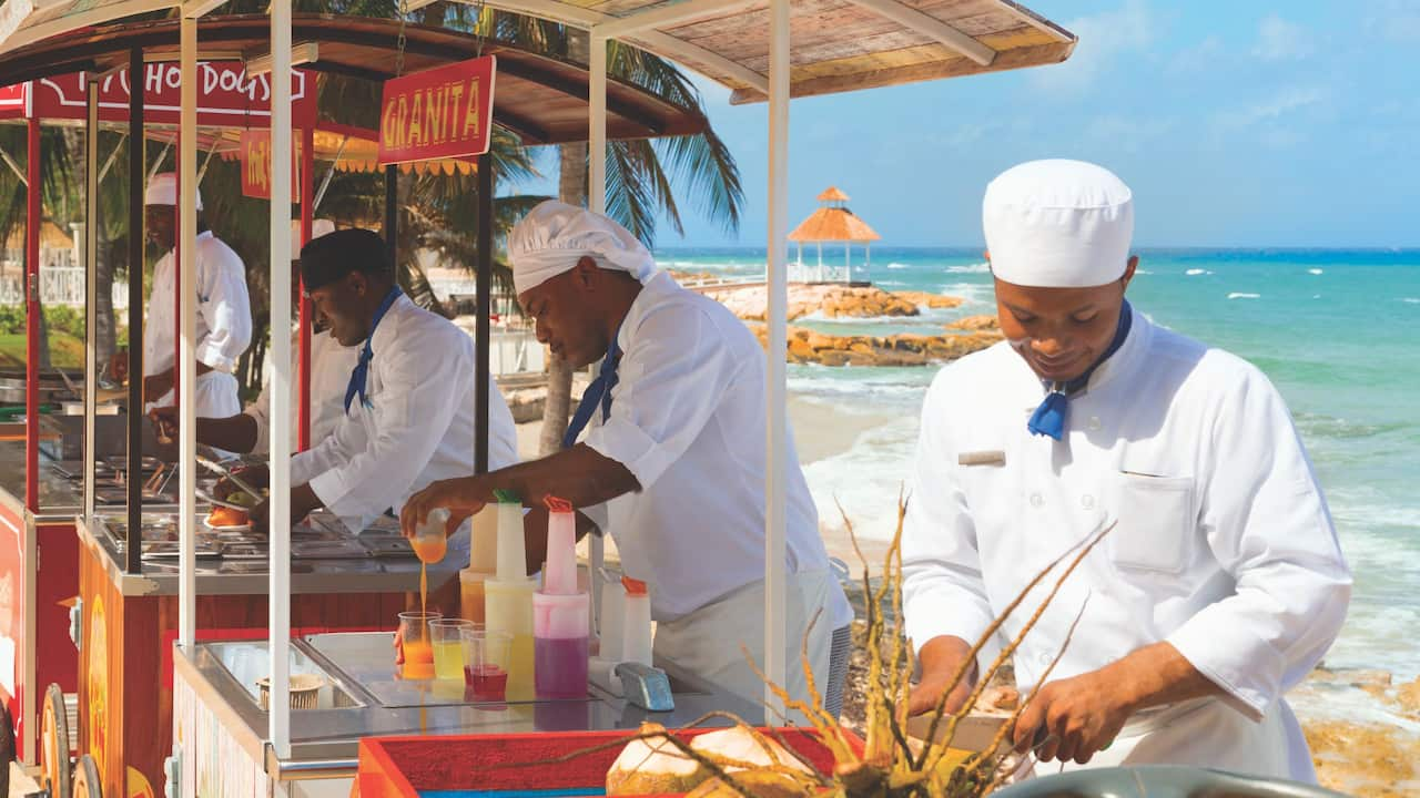 Cooks preparing food at food carts on beach