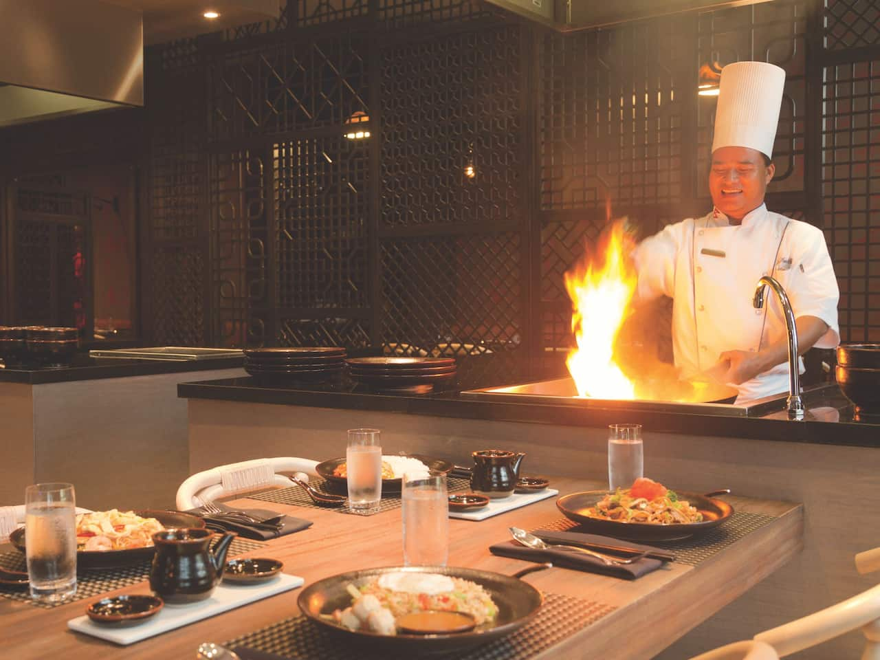 Chef cooking over open flame on restaurant grill in front of table at FuZion Asian Grill Hyatt Ziva Rose Hall