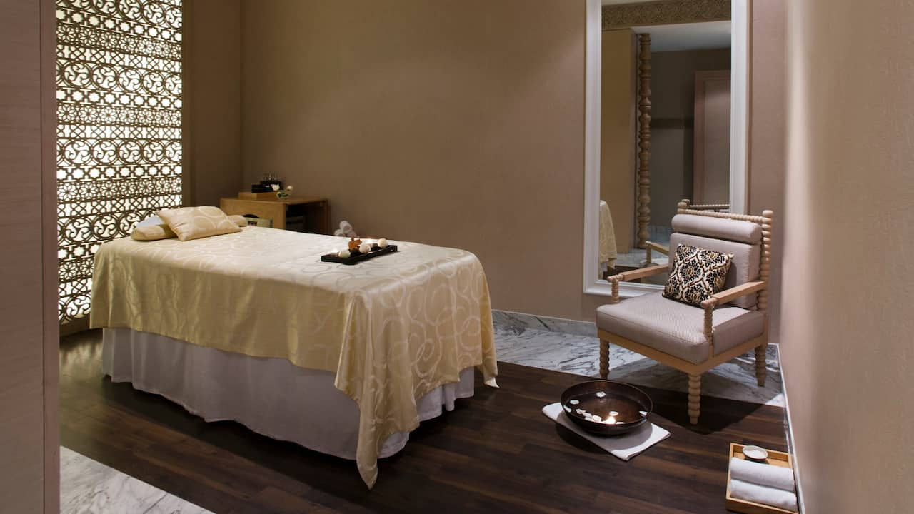 Relaxing spa treatment room with massage table