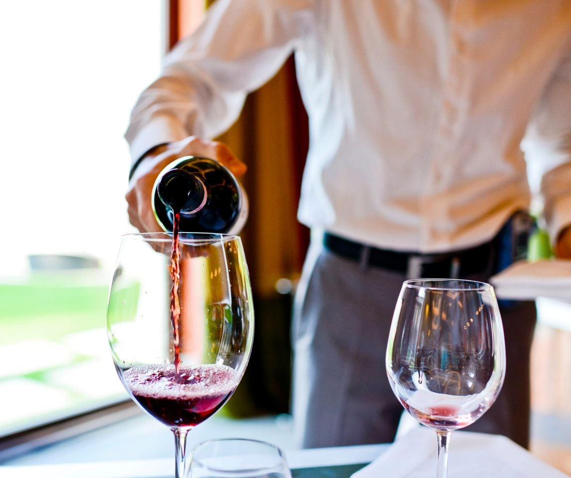 Server pouring red wine into glass