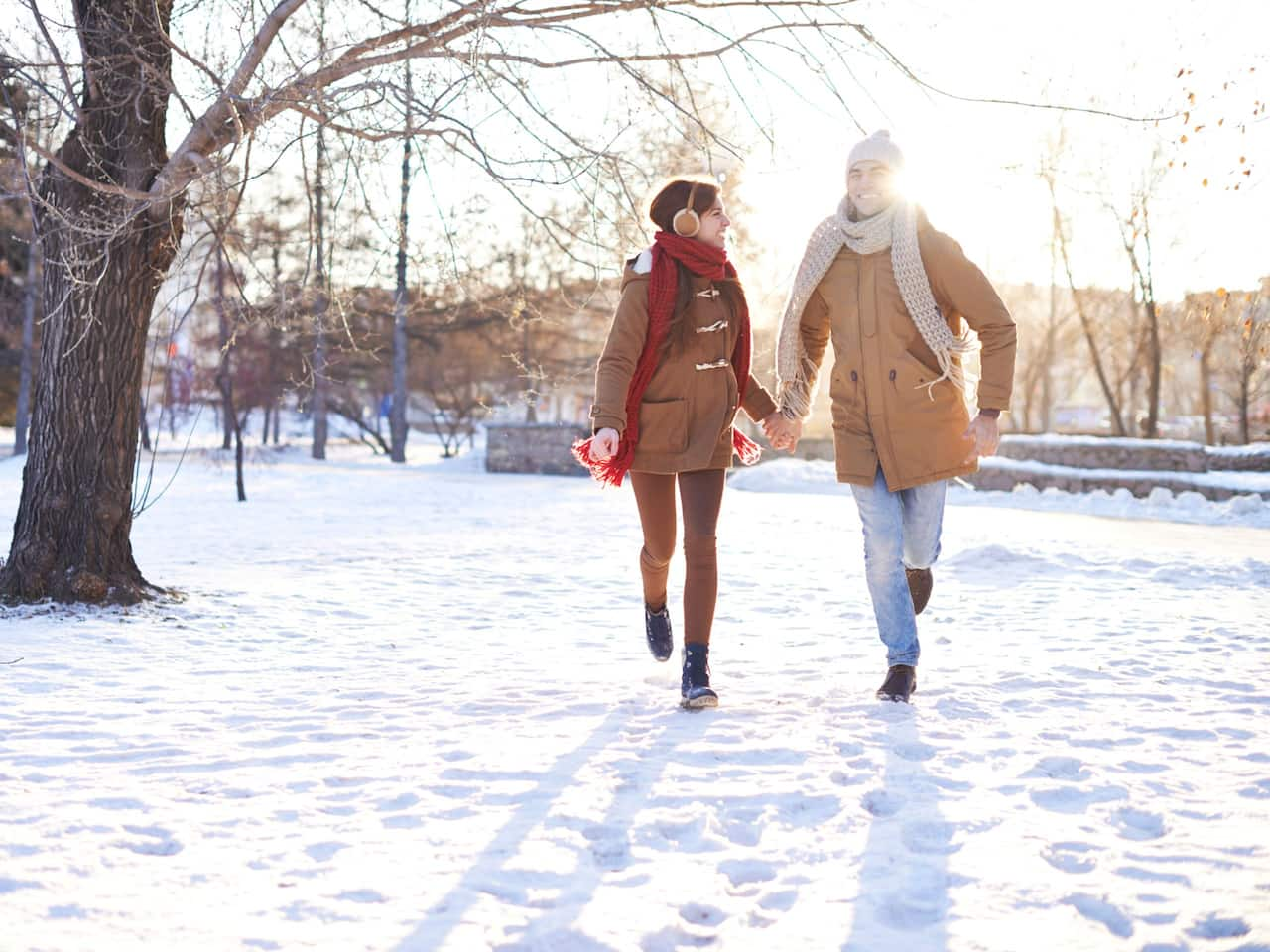 Couple running through snow