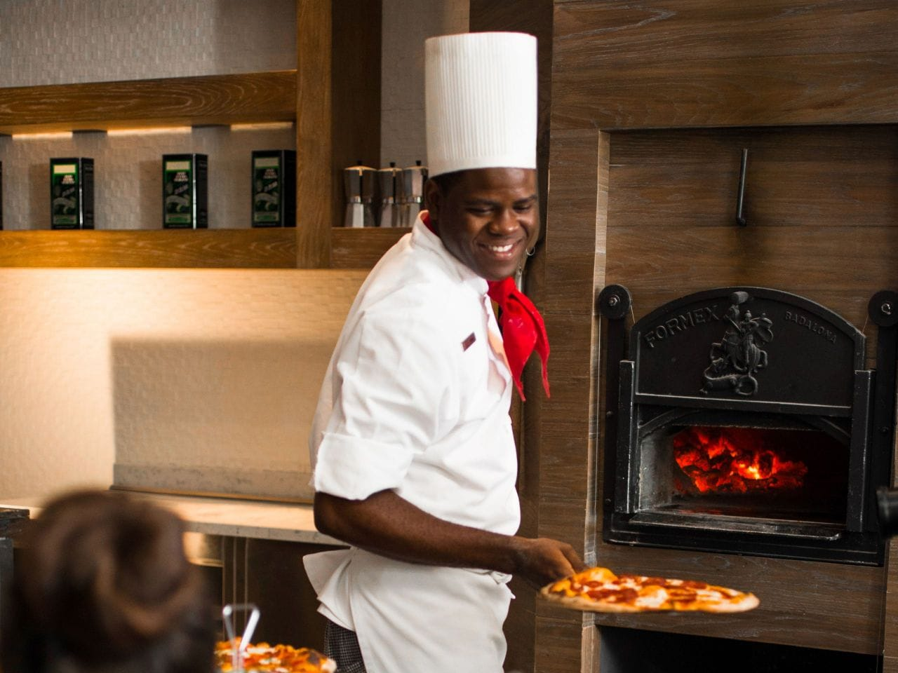 Chef removing pizza from oven at Di RoZa Italian Restaurant at Hyatt Ziva Rose Hall