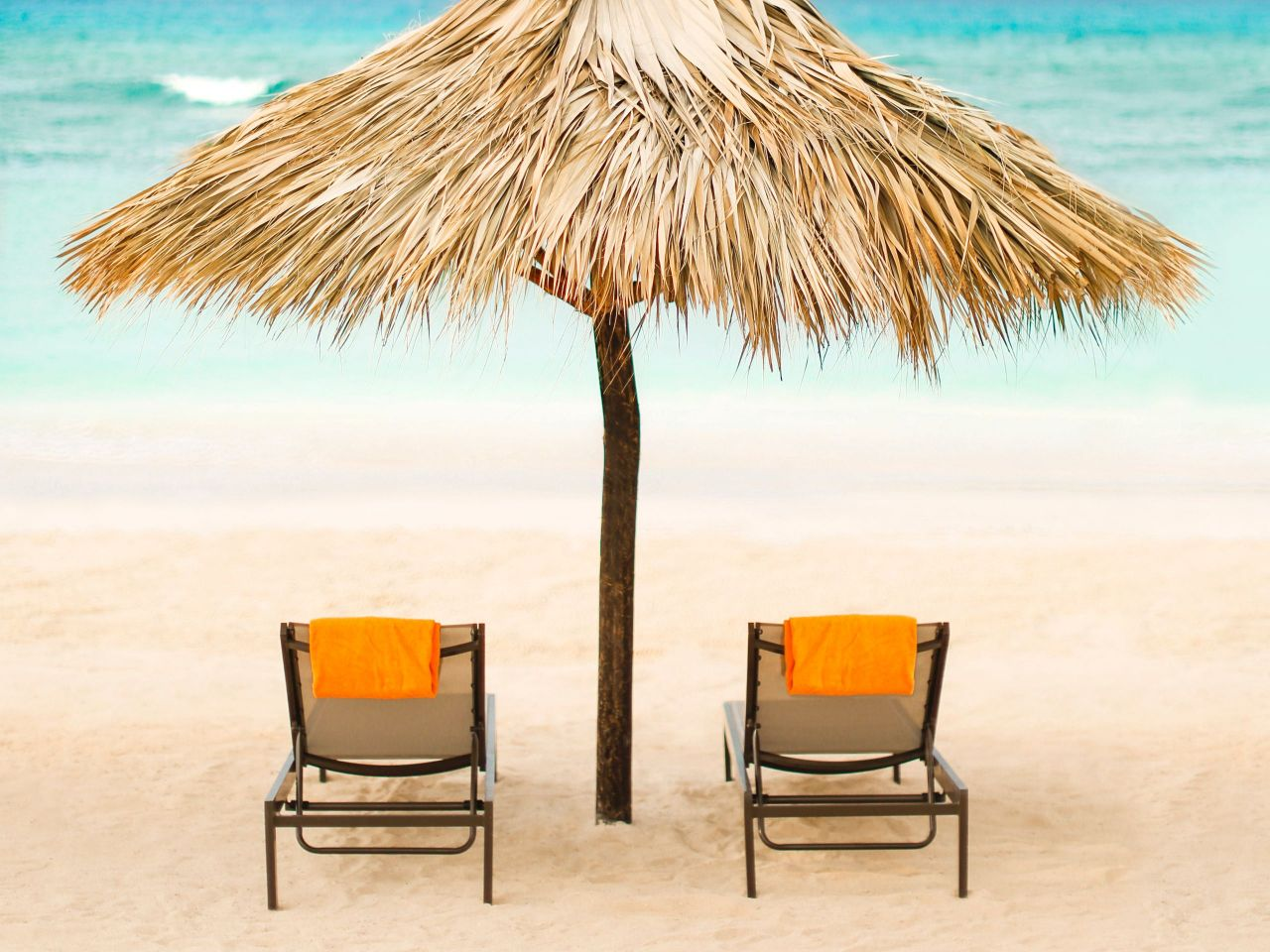 Two beach chairs under palm umbrella