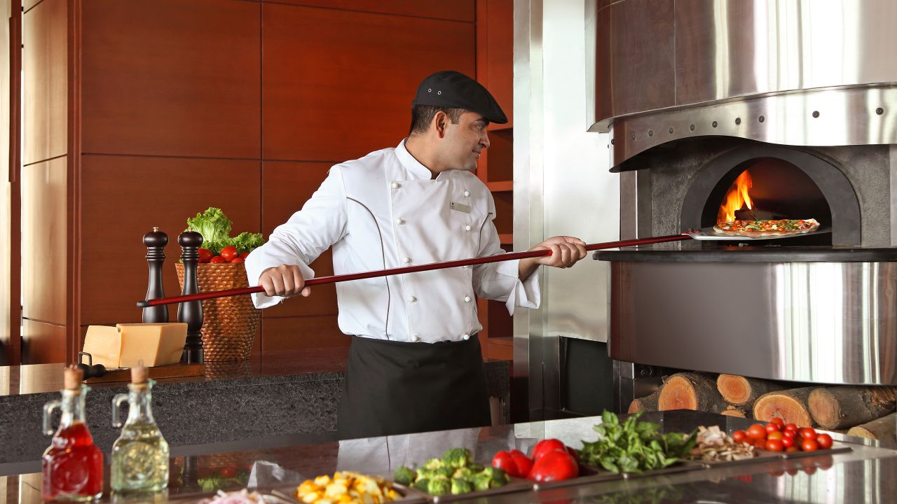 Chef putting pizza in oven with open flame