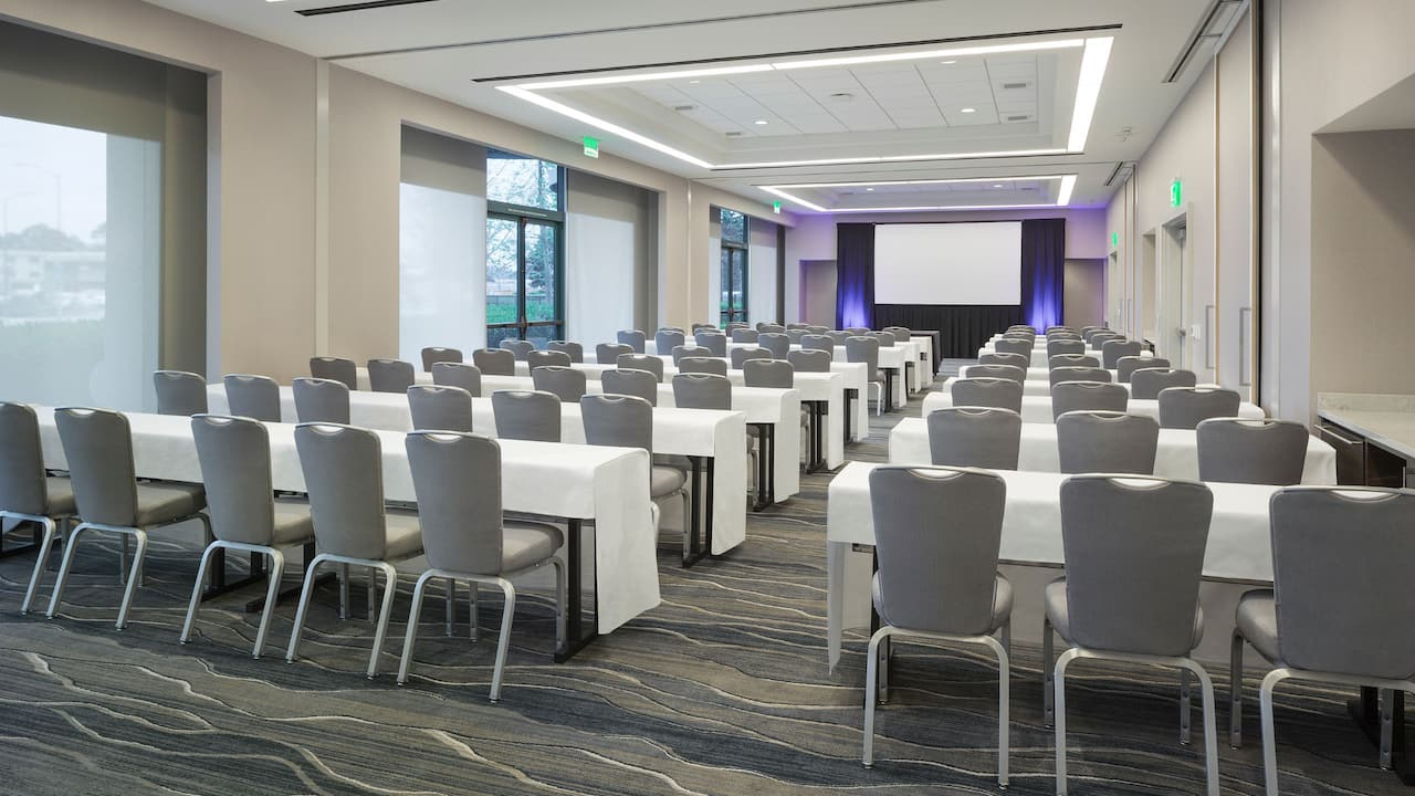 Rows of tables and chairs in ballroom classroom setup