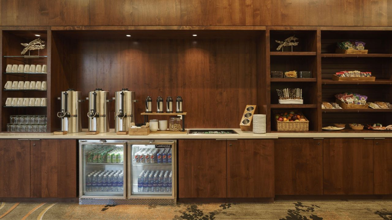 Wood cabinets, white counter with coffee dispensers, mini-refrigerators