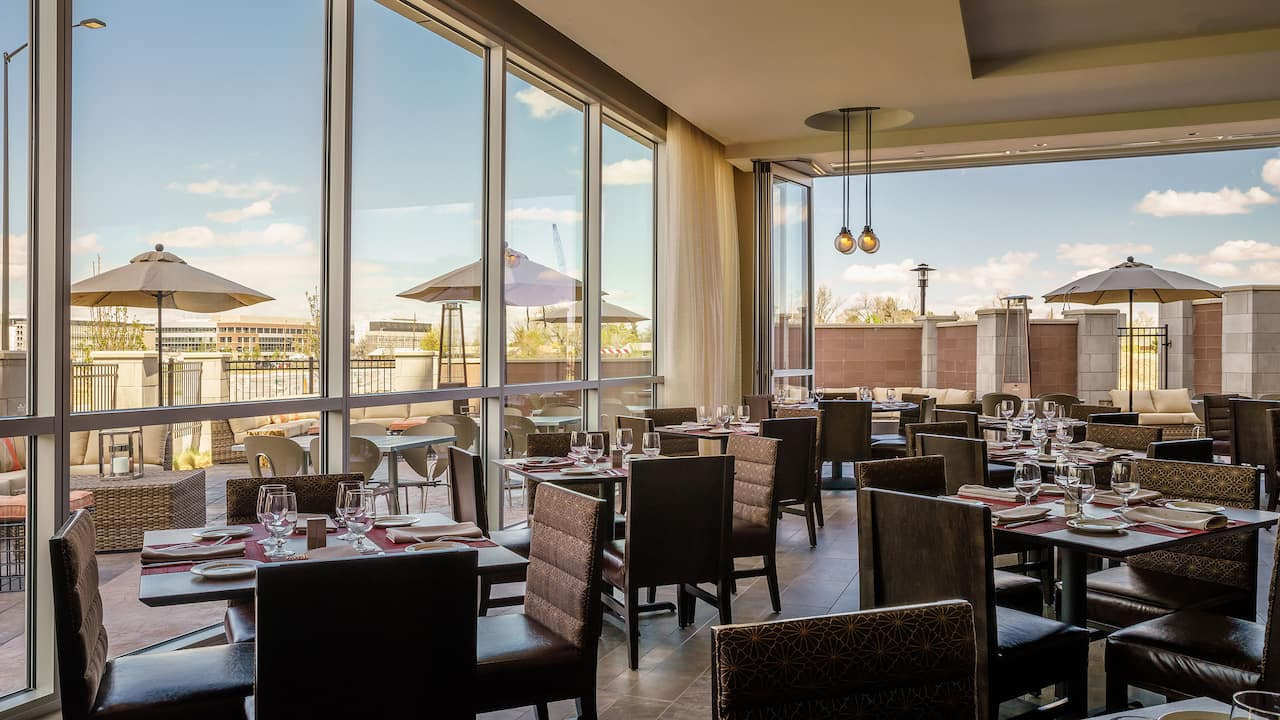 Tables and chairs by windows in hotel restaurant