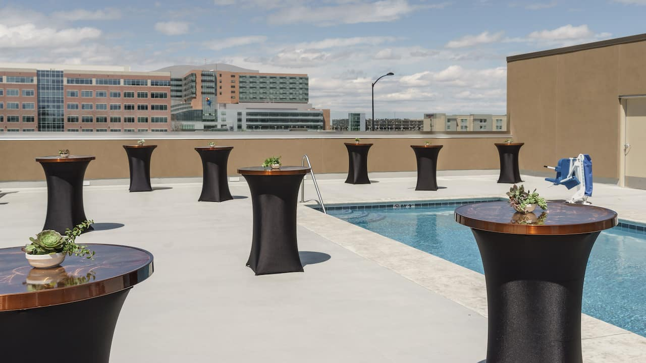 Tall bistro tables near pool on hotel rooftop