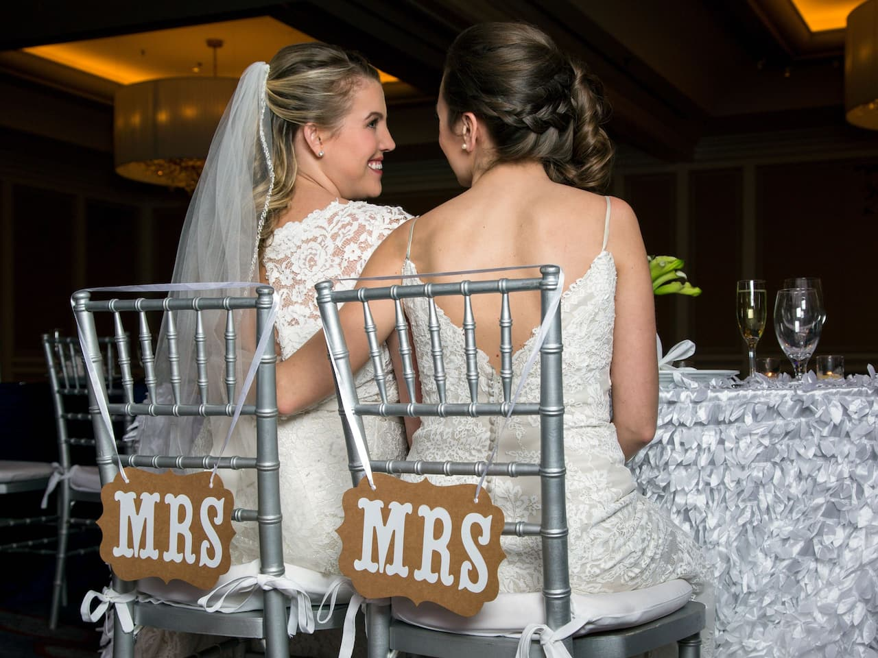 Two women in chairs with MRS signs at wedding