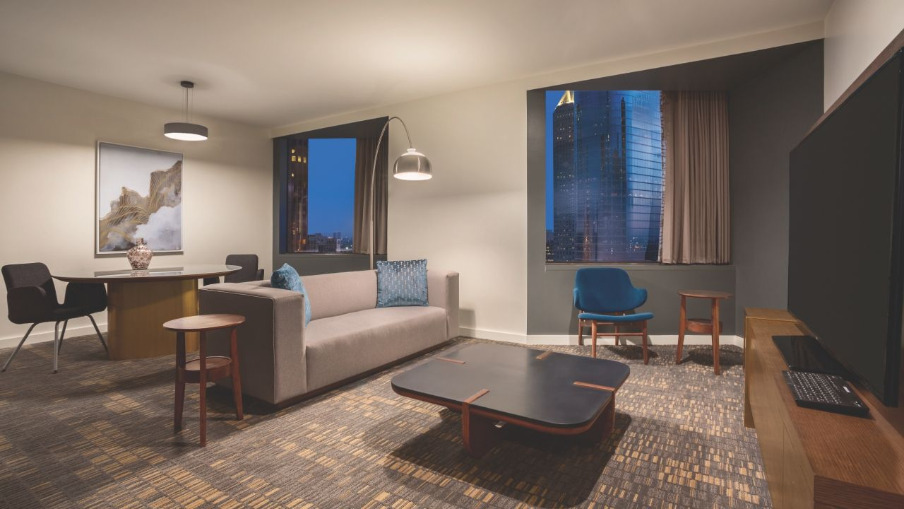 Hyatt Regency Houston imperial suite parlor with couch, dining area, and big screen TV