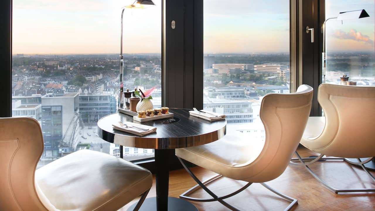 Table with two chairs at window overlooking Dusseldorf