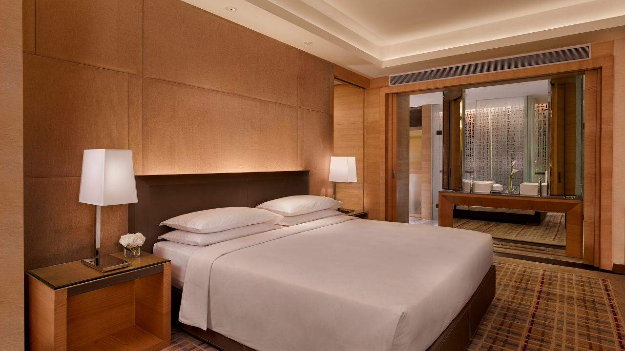 King sized bed between nightstands with lamps by window in hotel suite