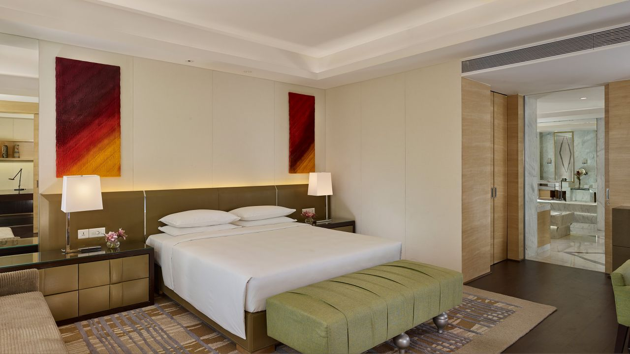King sized bed between nightstands with lamps in hotel suite