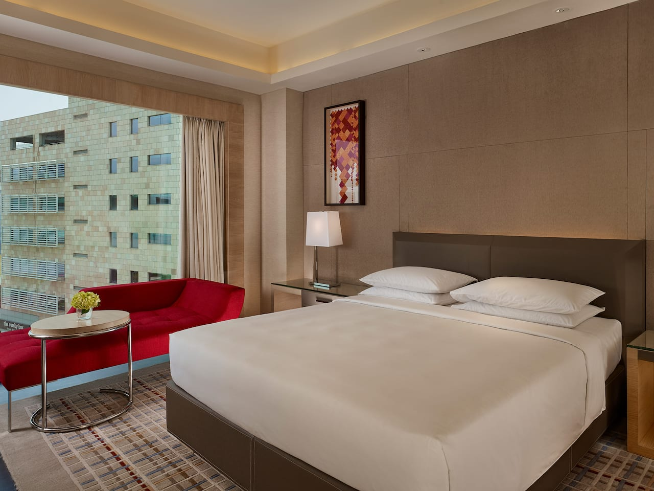 King sized bed by large window in hotel suite