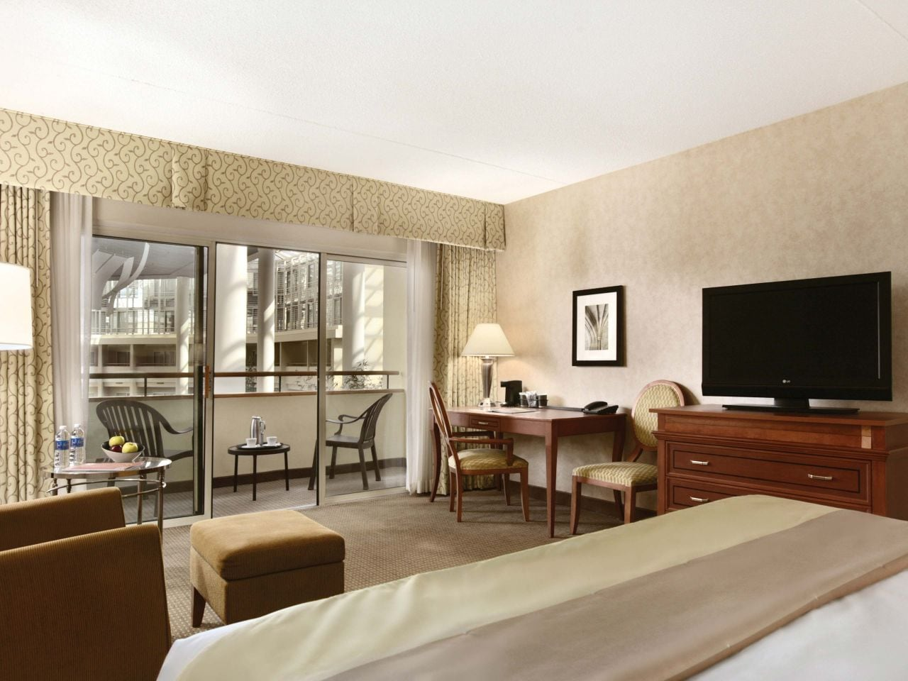 King-sized bed by large window with TV and armchair in hotel room