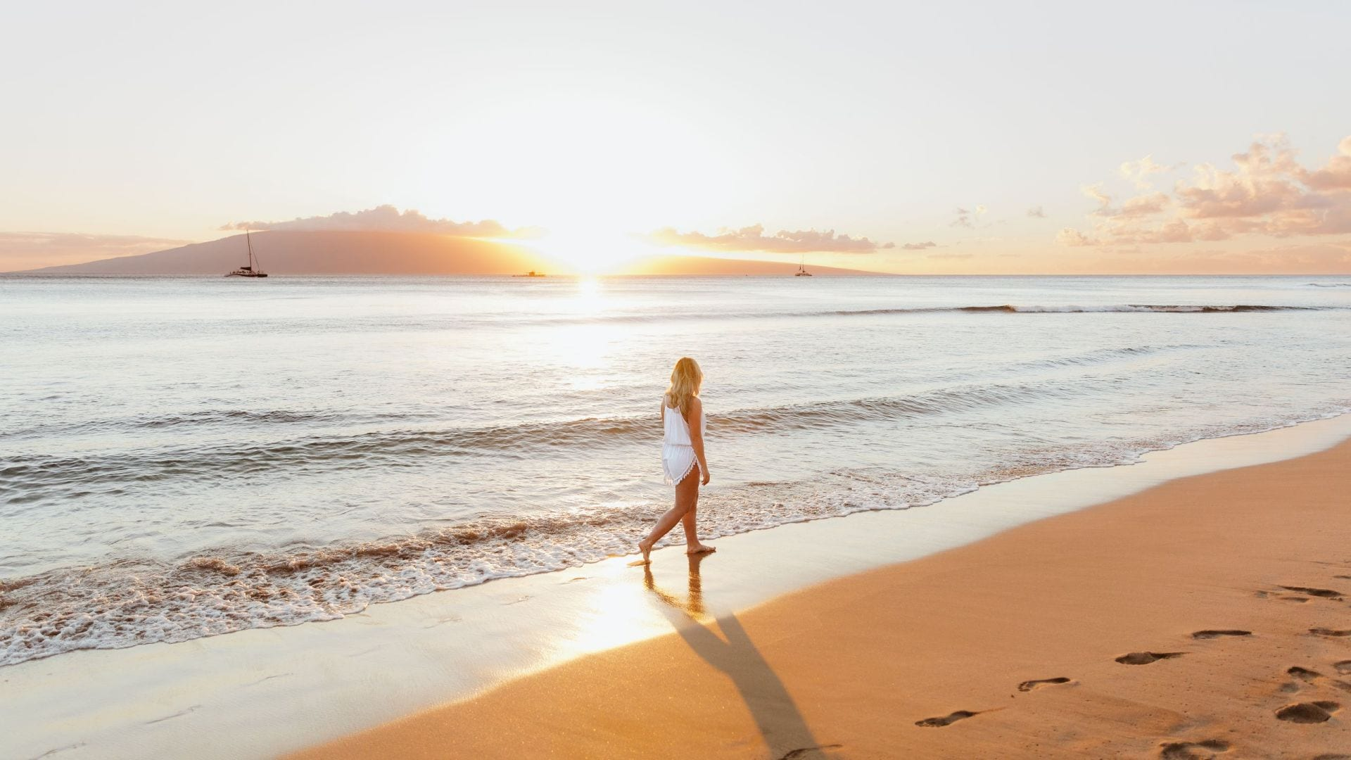 woman walking on beach at susnset