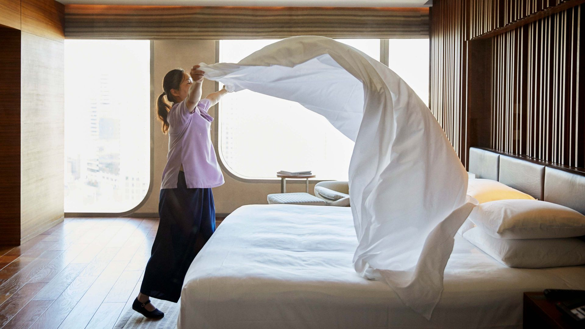 A hotel worker billows out a fresh sheet over a guest bed.
