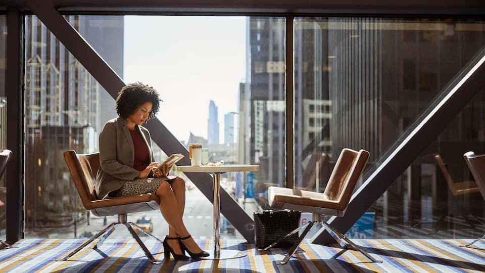 Woman working near window with city view