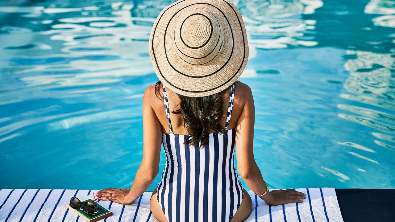 Woman sitting next to a Hyatt pool with her feet in the water