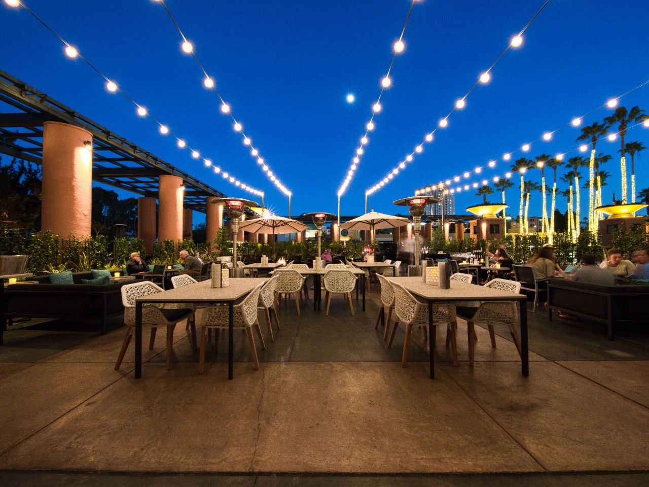 Row of set tables/chairs under patio lights at night