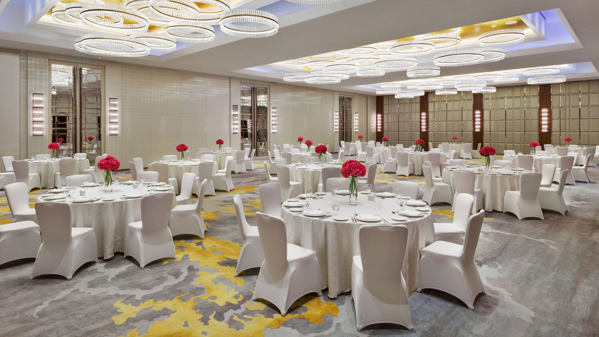 Wedding tables with place settings in hotel ballroom