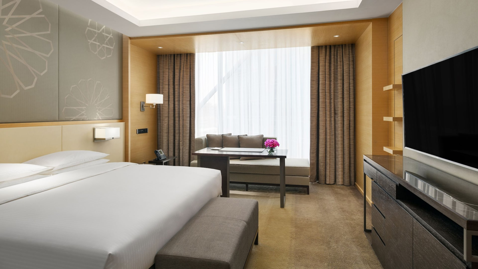 King-sized bed by large window with TV and sofa in hotel room
