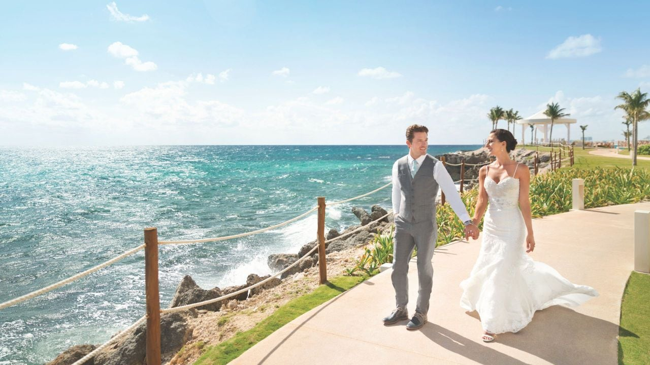 Bride and groom walking above beach