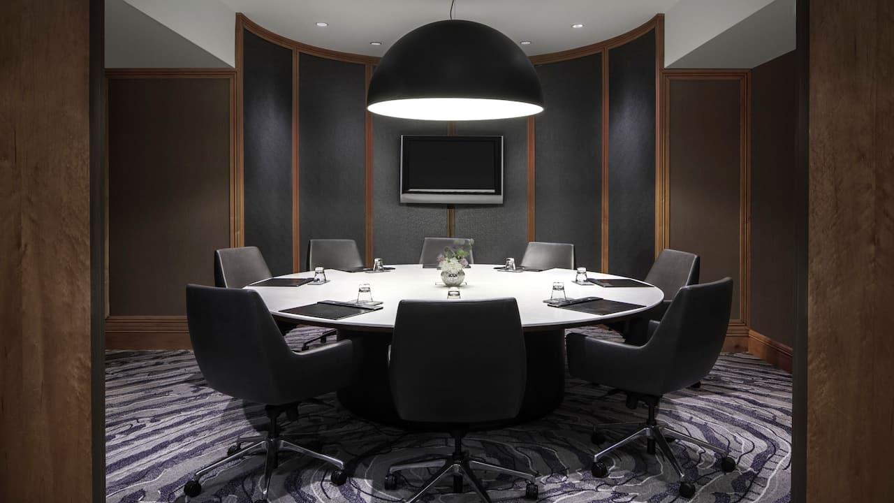 Large round table with executive chairs in meeting room