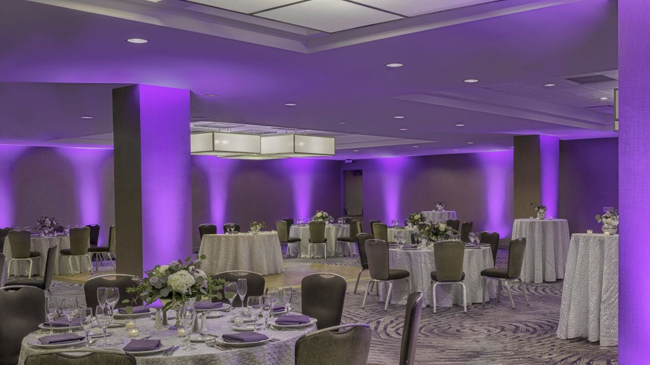Wedding tables set up with place settings and purple backdrop