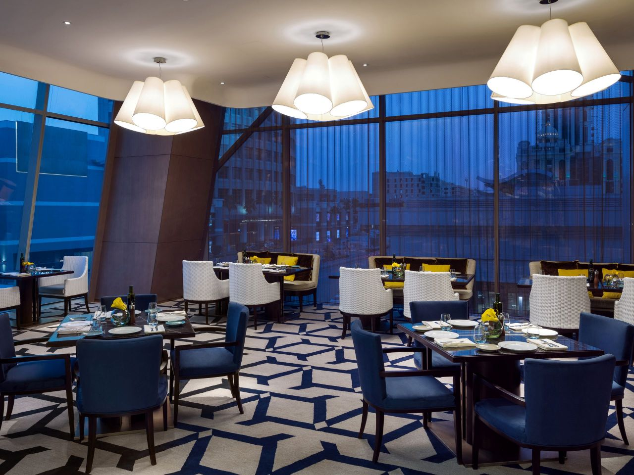 Tables and chairs by windows in hotel restaurant at night
